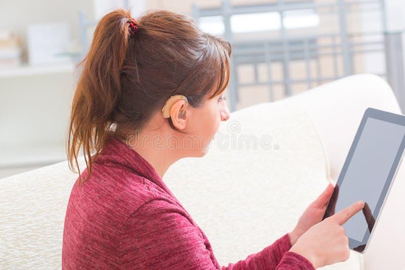 Donna sorda che per mezzo della compressa fotografia stock