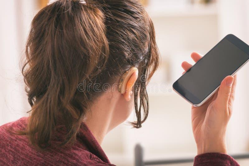 Donna sorda che per mezzo dello smartphone fotografie stock libere da diritti