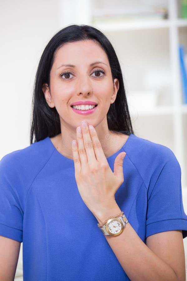 Donna sorda sorridente che usando linguaggio dei segni immagine stock libera da diritti