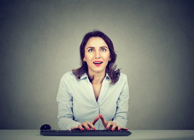Donna sorpresa che per mezzo di un computer fotografia stock libera da diritti