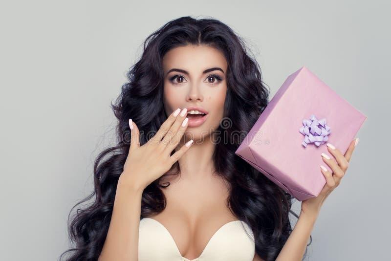 Donna sorpresa con il contenitore di regalo Bello modello con la bocca aperta fotografia stock libera da diritti