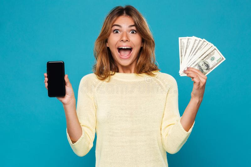 Donna sorpresa in maglione che mostra lo schermo in bianco dello smartphone immagini stock libere da diritti