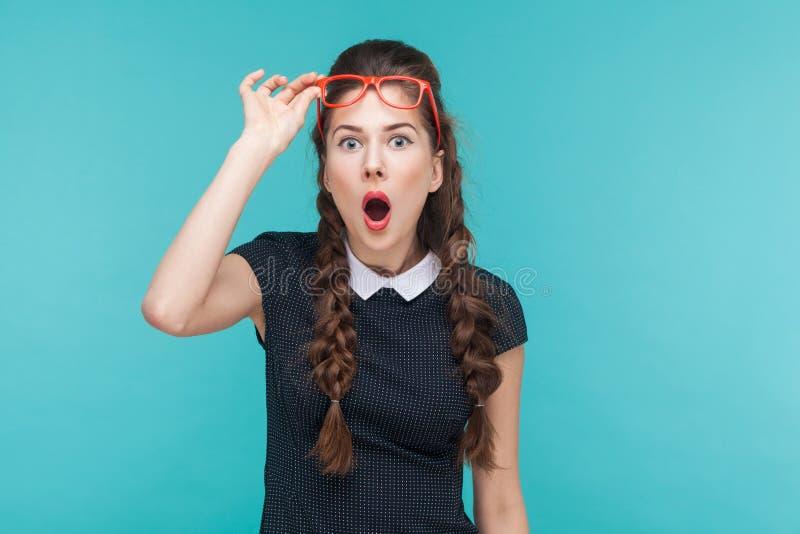 Donna sorpresa nella stupefazione rossa di vetro che esamina macchina fotografica immagini stock libere da diritti