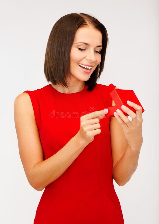 Donna sorpresa in vestito rosso con il contenitore di regalo immagini stock libere da diritti