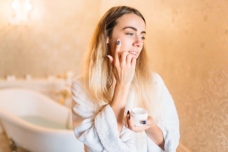 Donna sorridente in accappatoio bianco, skincare facciale fotografie stock libere da diritti