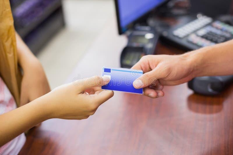 Donna sorridente al registratore di cassa che paga con la carta di credito fotografia stock