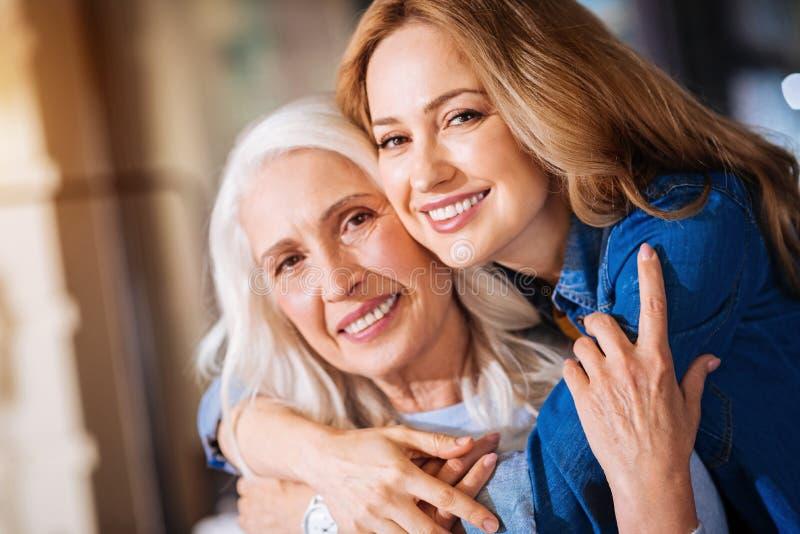Donna sorridente allegra che abbraccia sua nonna anziana immagini stock