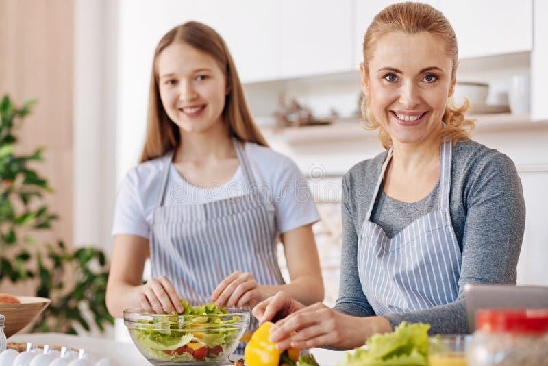 Donna sorridente allegra che cucina con sua figlia fotografia stock libera da diritti