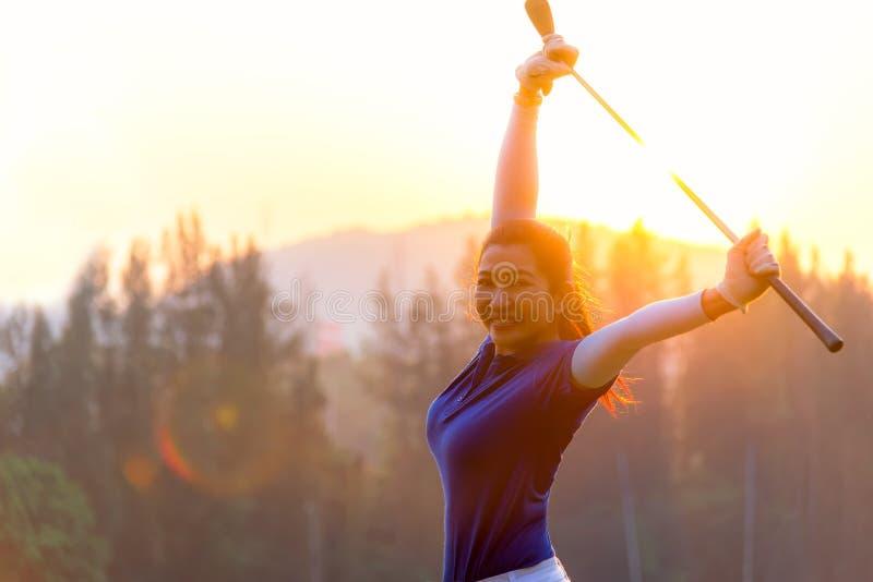 Donna sorridente asiatica felice allegra con un golf nel club di golf nel tempo soleggiato e perfino di tramonto, spazio della co fotografia stock