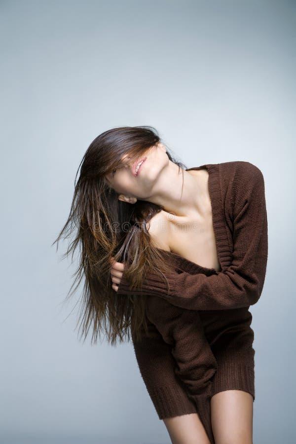 Donna sorridente attraente con capelli lunghi su grey fotografia stock