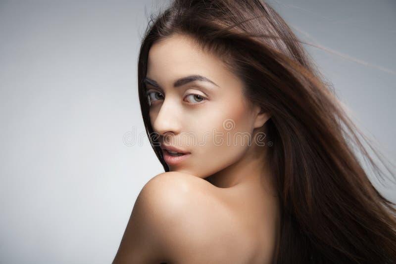 Donna sorridente attraente con capelli lunghi su grey immagini stock libere da diritti