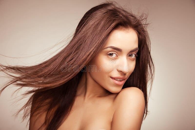 Donna sorridente attraente con capelli lunghi su grey fotografie stock