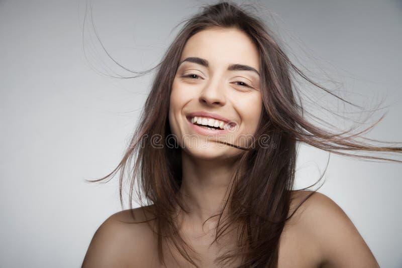 Donna sorridente attraente con capelli lunghi su grey immagini stock