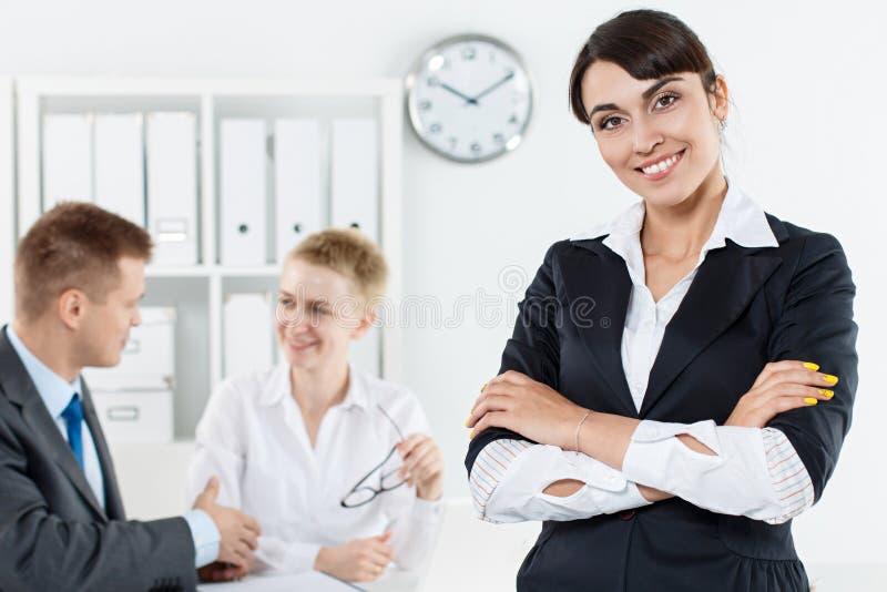 Donna sorridente bella di affari in vestito che sta con l'Ass.Comm. delle mani immagine stock