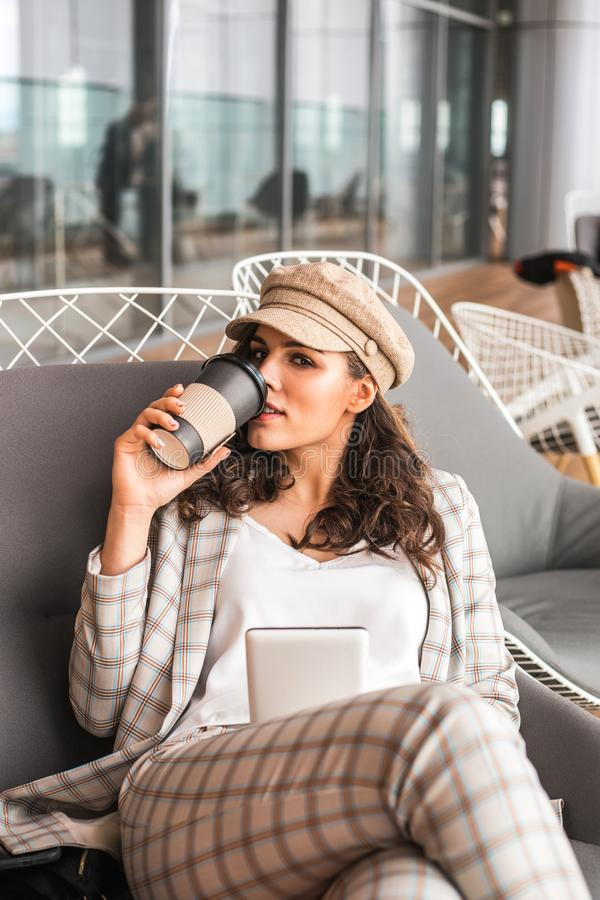 Donna sorridente in caff? dell'aeroporto con la tazza di caff? fotografia stock