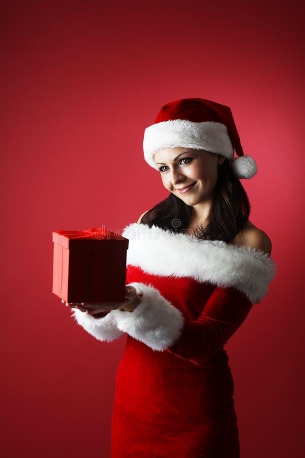 Donna sorridente in cappello dell'assistente di Santa con la parte anteriore del contenitore di regalo di fondo rosso immagini stock libere da diritti