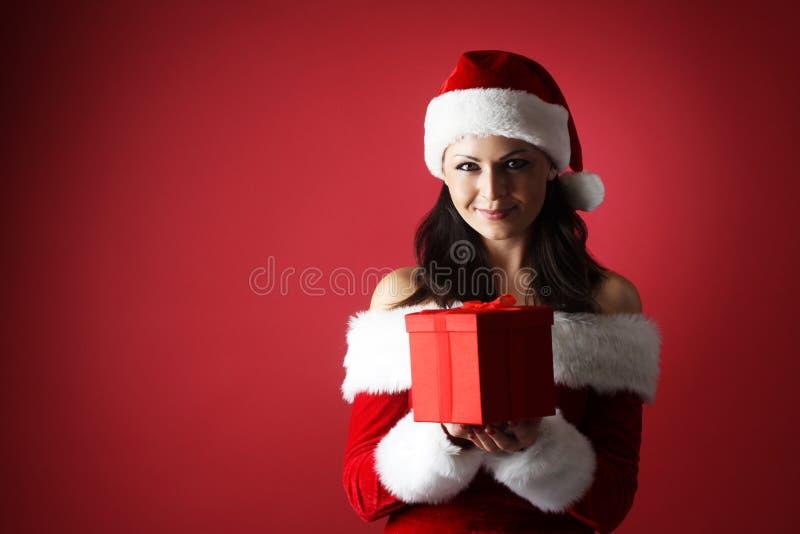 Donna sorridente in cappello dell'assistente di Santa con la parte anteriore del contenitore di regalo di fondo rosso fotografie stock