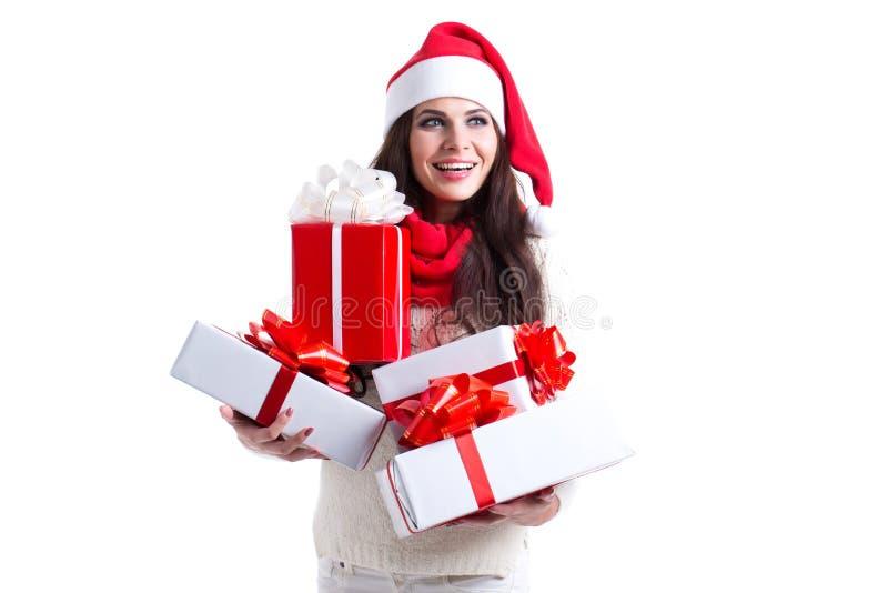 Donna sorridente in cappello dell'assistente di Santa con molti contenitori di regalo immagine stock