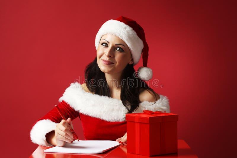 Donna sorridente in cappello dell'assistente di Santa e vestiti del Babbo Natale con il contenitore di matita e della carta e di  fotografie stock