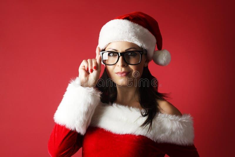 Donna sorridente in cappello dell'assistente di Santa, vestiti e vetri neri davanti a fondo rosso fotografia stock