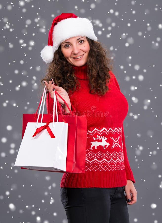 Donna sorridente in cappello di Santa con i sacchetti della spesa fotografia stock