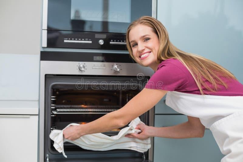 Donna sorridente casuale che mette il vassoio di cottura in forno immagine stock libera da diritti