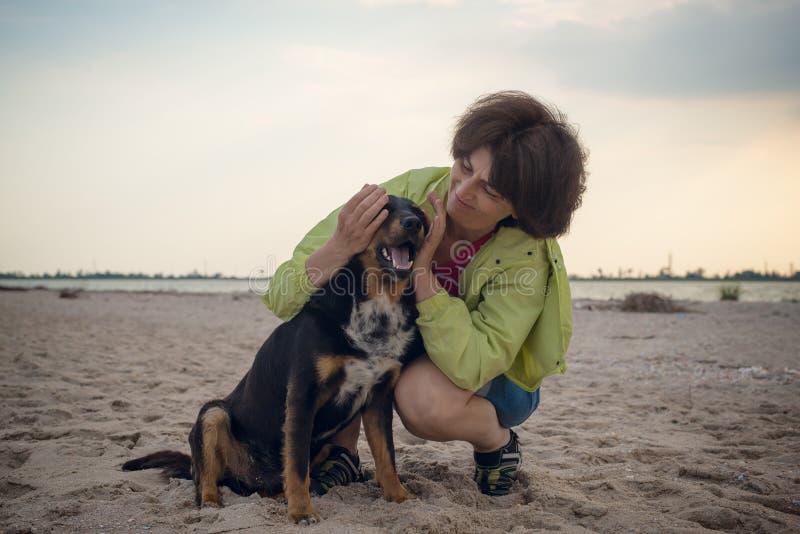 Donna sorridente che abbraccia con un cane fotografia stock