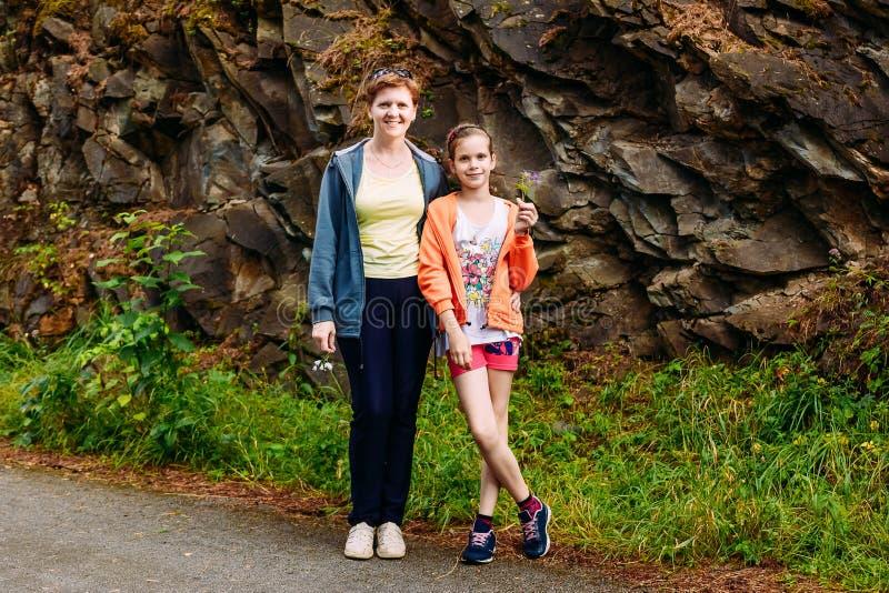 Donna sorridente che abbraccia figlia di dieci anni immagini stock libere da diritti