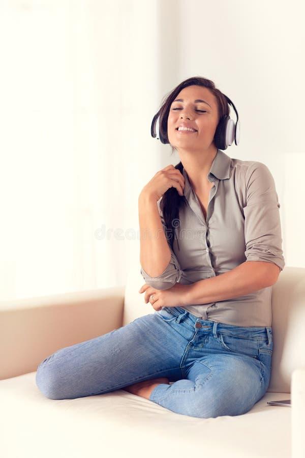 Donna sorridente che ascolta la musica con le cuffie immagini stock