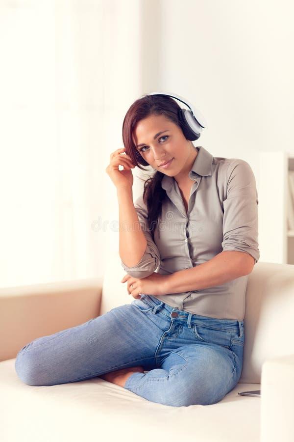 Donna sorridente che ascolta la musica con le cuffie fotografie stock libere da diritti