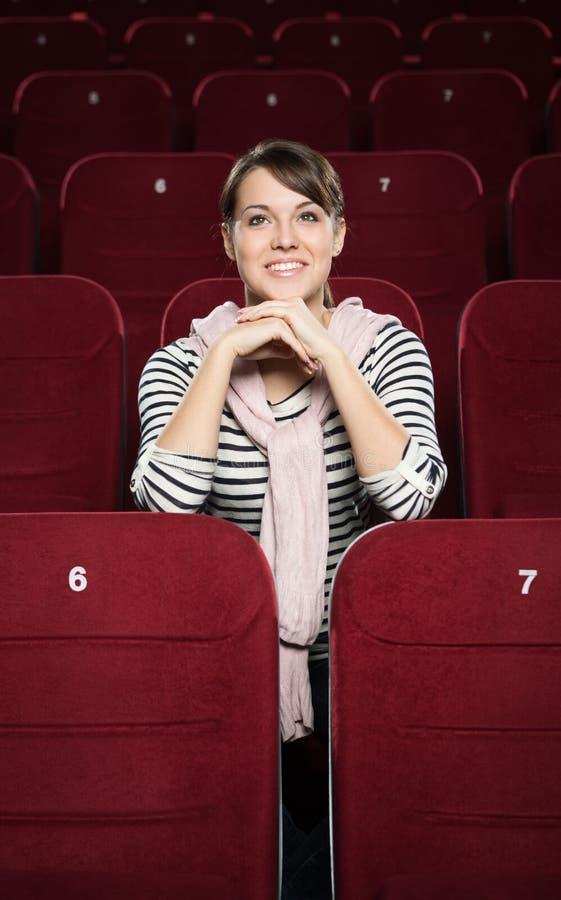 Donna sorridente che attende un film fotografie stock