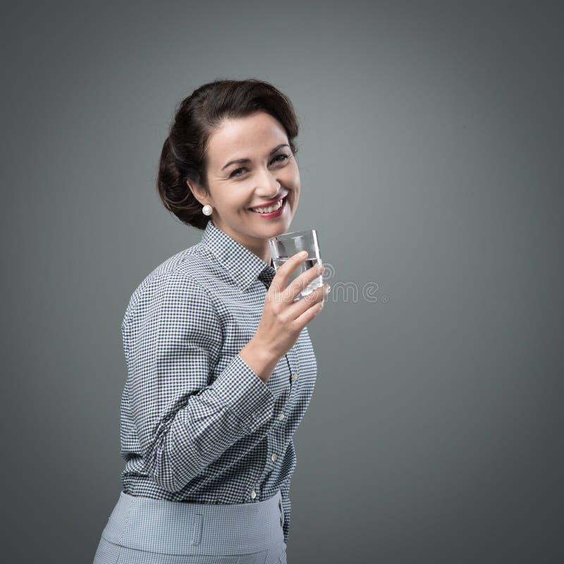 Donna sorridente che beve un bicchiere d'acqua fotografia stock