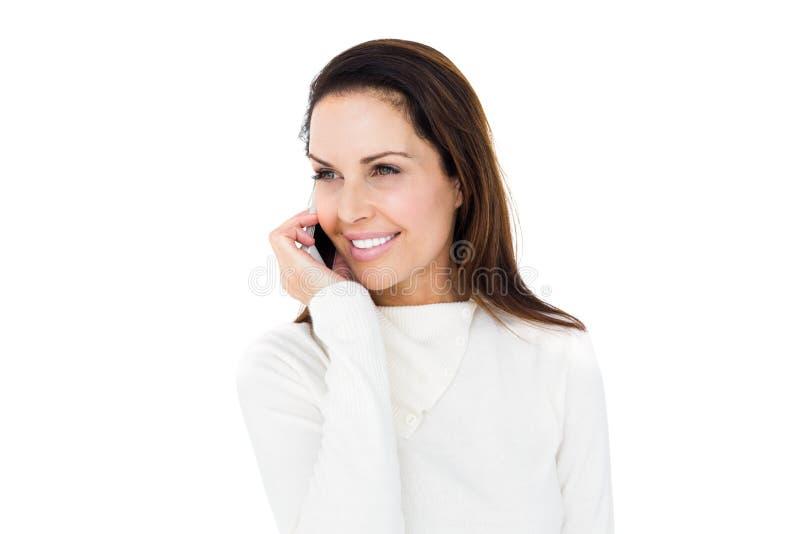 Donna sorridente che chiama con il suo smartphone fotografia stock