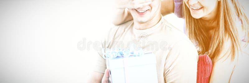 Donna sorridente che dà un presente al suo ragazzo fotografia stock