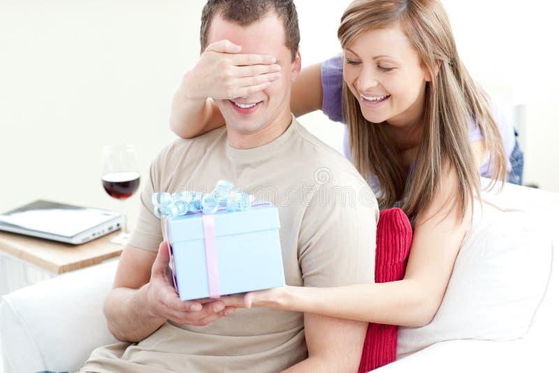 Donna sorridente che dà un presente al suo ragazzo immagine stock