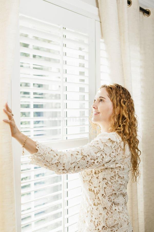 Donna sorridente che guarda fuori finestra fotografia stock libera da diritti
