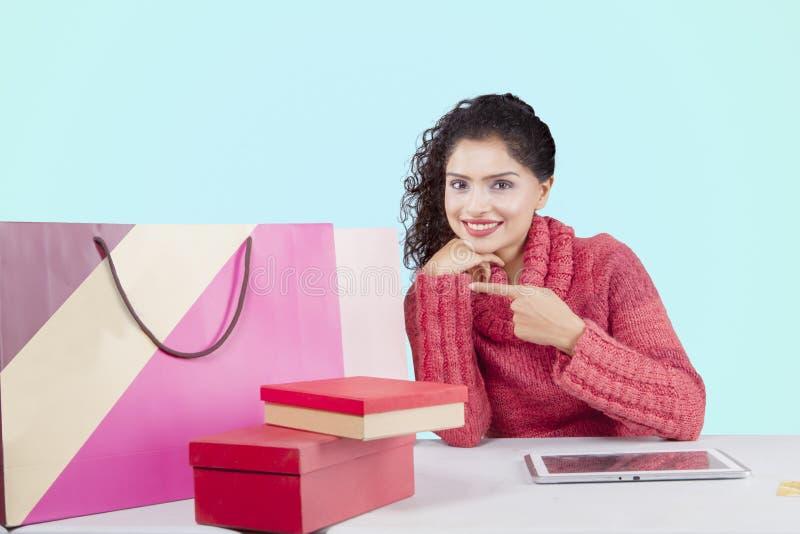 Donna sorridente che indica i sacchetti della spesa sullo studio fotografie stock libere da diritti