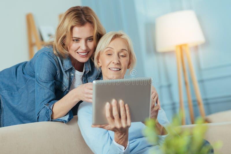 Donna sorridente che insegna a sua nonna a come utilizzare un dispositivo moderno immagine stock