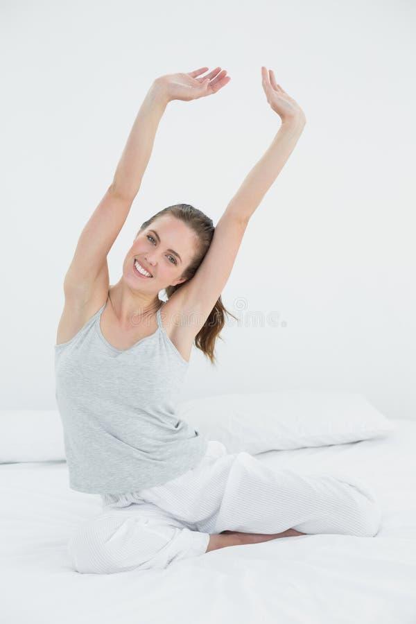 Donna sorridente che la allunga armi su a letto fotografia stock libera da diritti