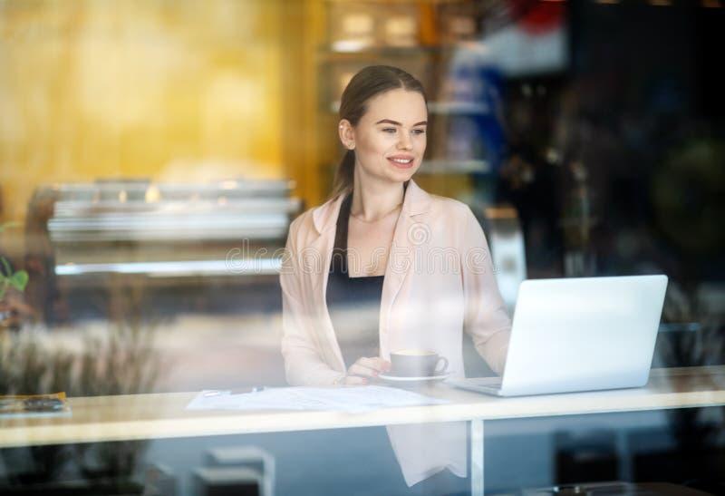 Donna sorridente che lavora al computer portatile alla caffetteria Riflessioni della finestra Sparato di una giovane donna che ut fotografia stock libera da diritti