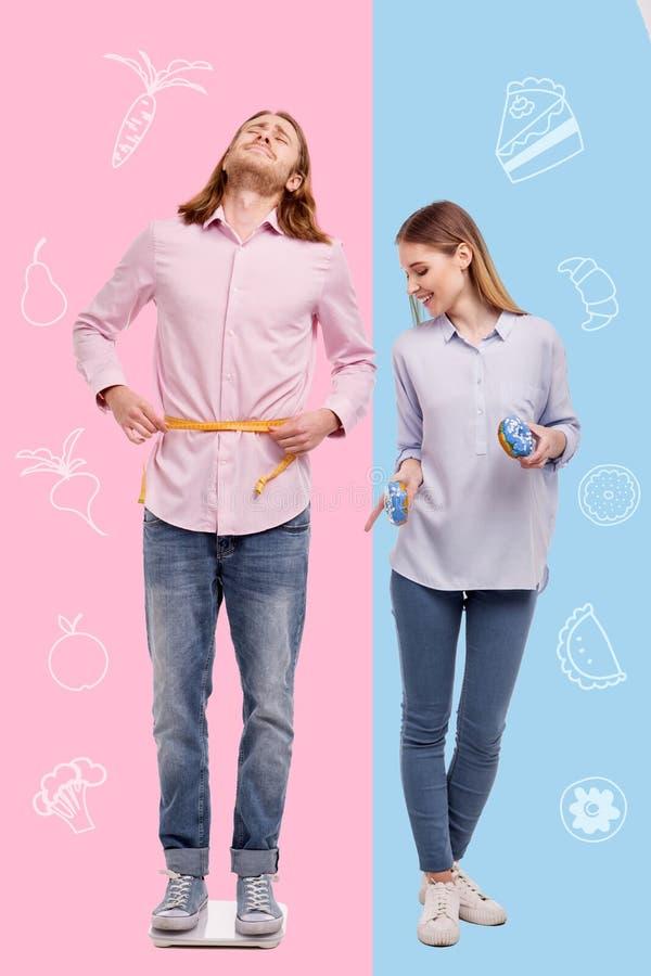 Donna sorridente che mangia i dolci mentre il suo marito preoccupato che è su una dieta immagine stock