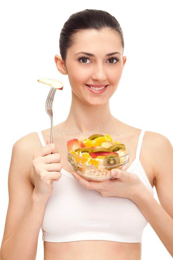 Donna sorridente che mangia un'insalata di frutta fotografia stock libera da diritti