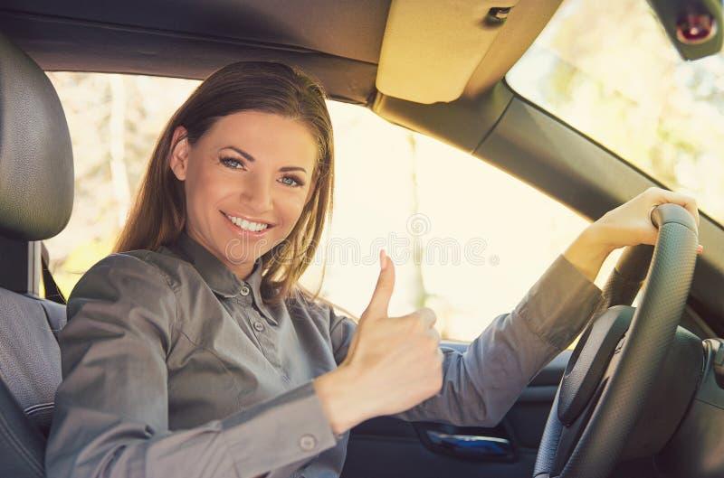 Donna sorridente che mostra pollice su in automobile fotografia stock