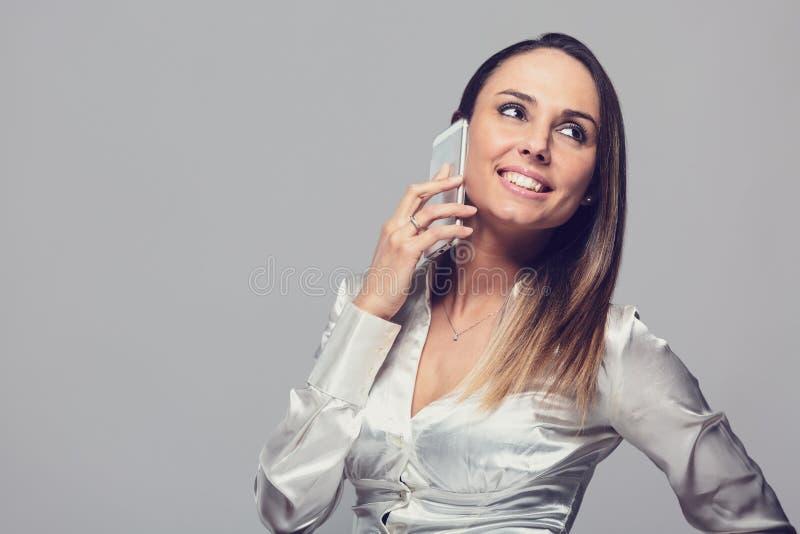 Donna sorridente che parla sullo smartphone immagini stock libere da diritti
