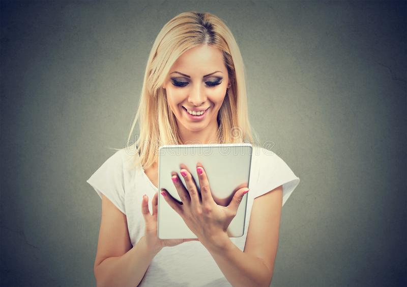 Donna sorridente che per mezzo della compressa moderna fotografia stock