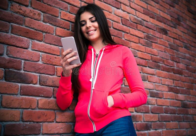 Donna sorridente che per mezzo dello smartphone immagine stock libera da diritti