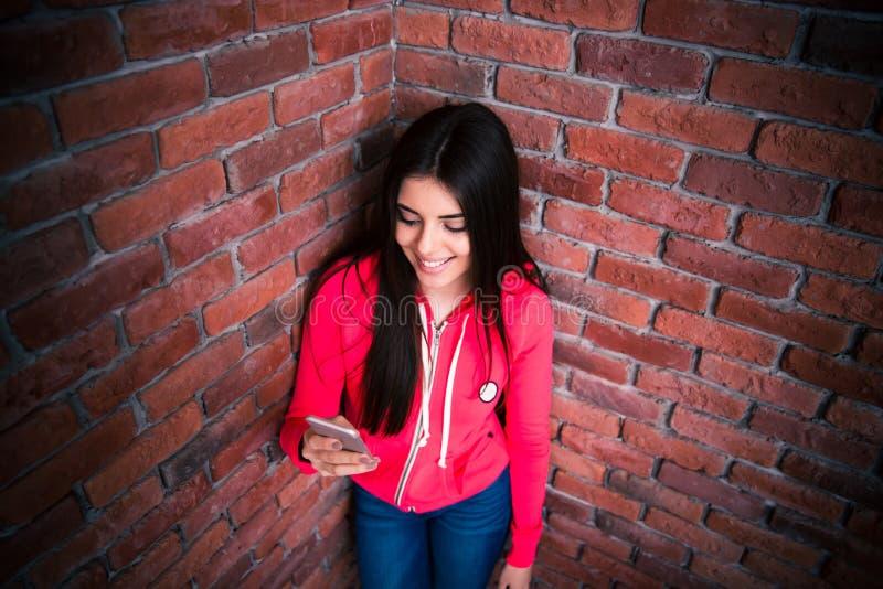 Donna sorridente che per mezzo dello smartphone fotografia stock