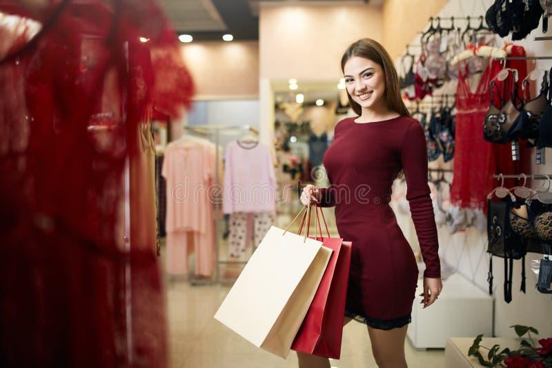 Donna sorridente che porta alcuni sacchetti della spesa con la vetrina del deposito della biancheria sui precedenti Ragazza cauca fotografia stock