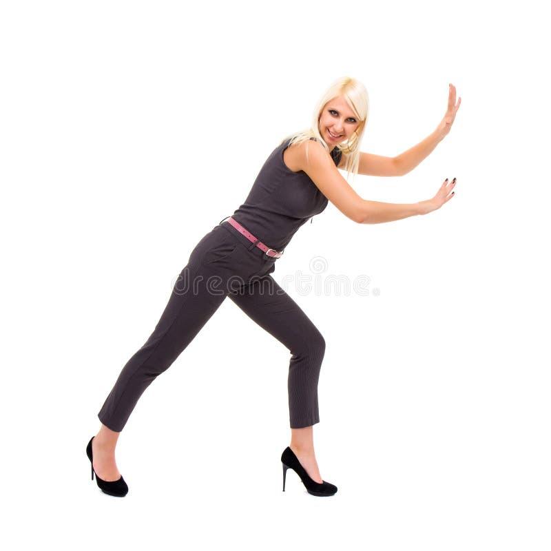 Donna sorridente che porta una tuta alla moda con il gestur della tenuta immagini stock