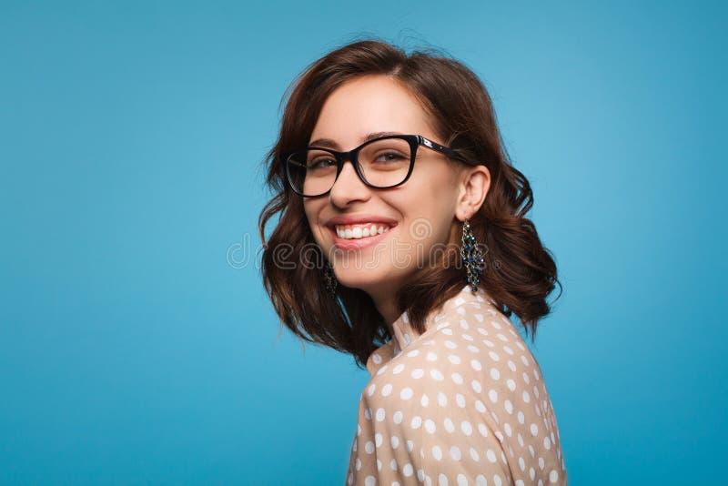 Donna sorridente che posa in vetri fotografia stock